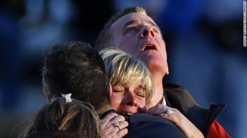 People weep and embrace near Sandy Hook Elementary School on Friday, December 14. Photo: CNN